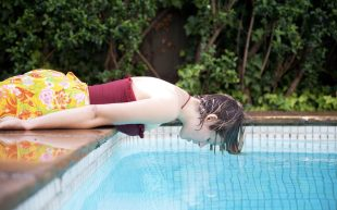 Woman looks into pool pondering future. Sarah Walker Photography.