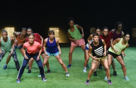performers facing the audience on stage in a sporting formation as if on a soccer field
