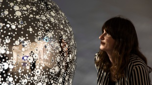 a woman looking at a shiny round reflective sculpture in a gallery