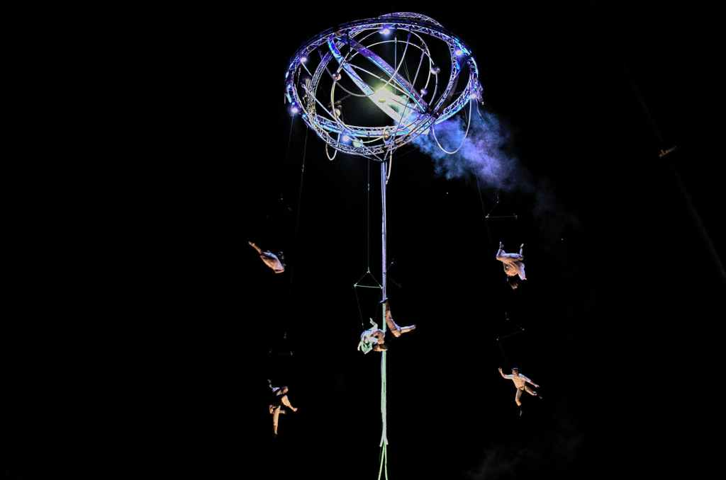 acrobats falling through the air at night-time performance