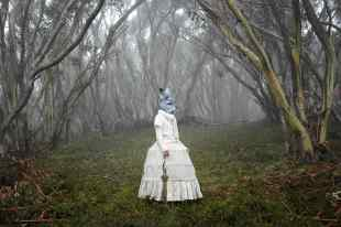 Woman in Australian bush with Victorian dress and rabbit headdress..