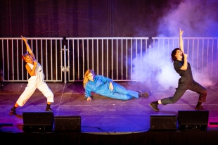 three young female performers in boiler suits onstage with micirphones