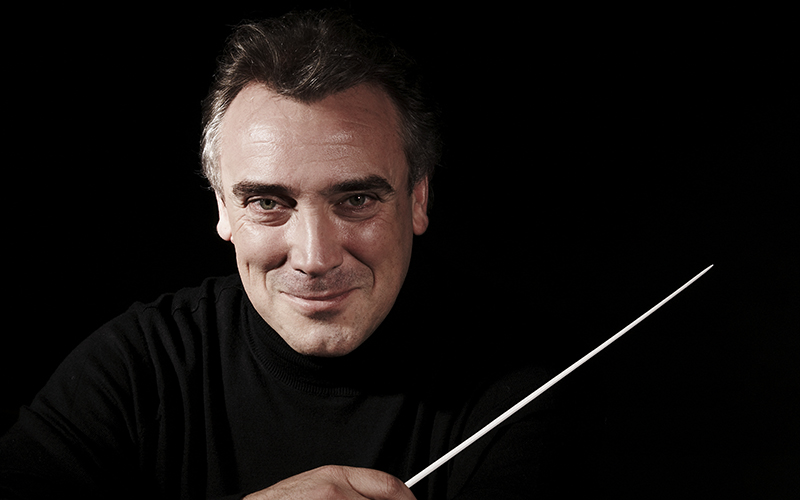 Man dressed in black on a black background holding a baton.