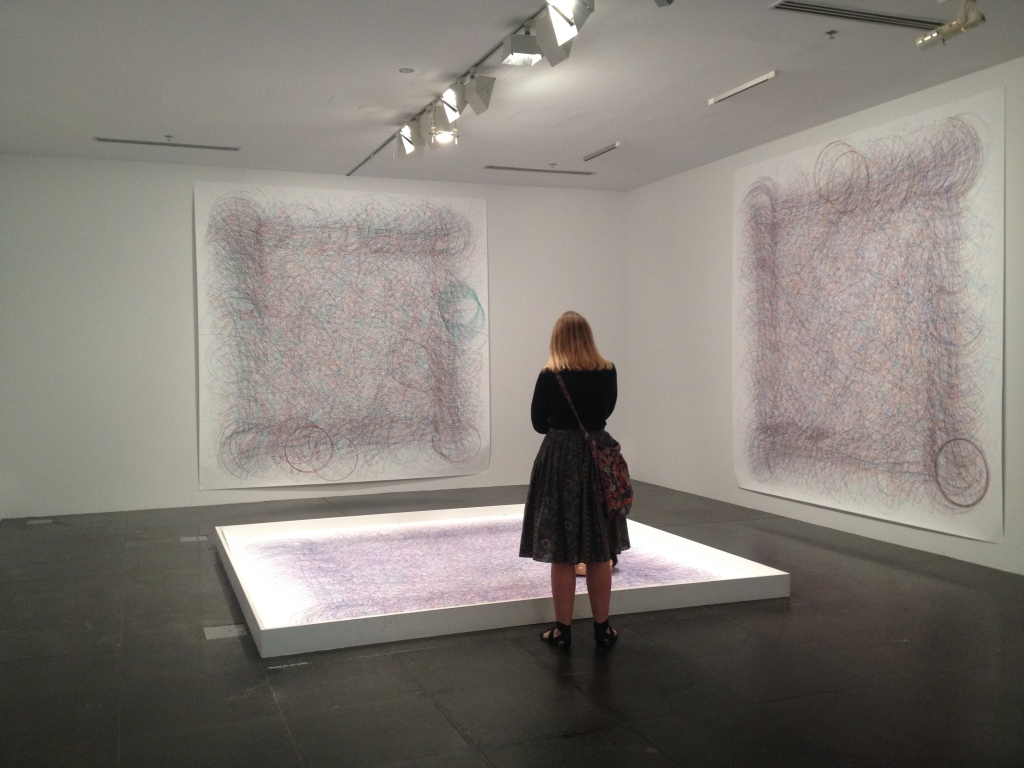 Woman in gallery looking at abstract painting.