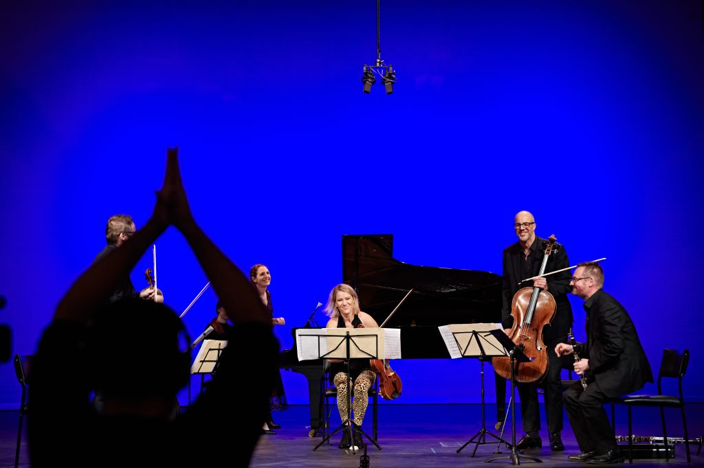 a group of classical musicans on stage and an audio engineer recording their concert
