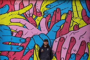 Indigenous person standing in front of a colourful mural
