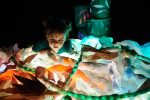 a child playing with coloured paper in the dark