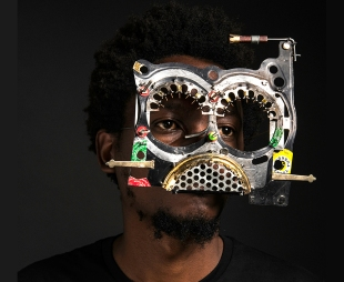 An African man wearing colourful glasses made from discarded car parts