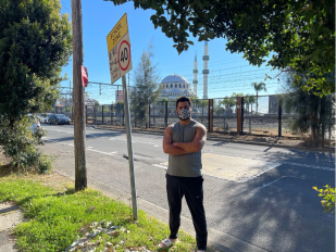 A man with crossed arms and face mask stands in front of a road with a mosque in the background