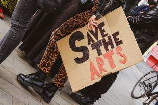 Person in leopard-print pants holds a sign saying Save the arts