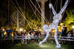 a giant puppet made of wire being manipulated by puppeteers in a park at night
