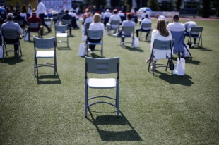 maintain the social distance during the Covid-19 outbreak at an outdoor event on the turf of a stadium.